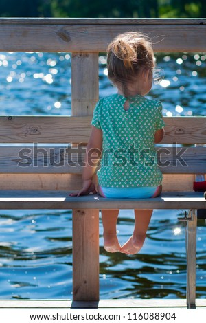 Cute child sitting on the bank on the pier - stock photo