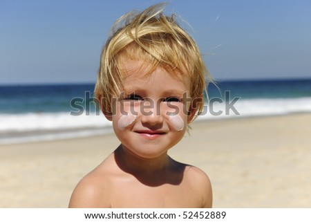 cute child sunbathing with sunscreen in her face at the beach smiling