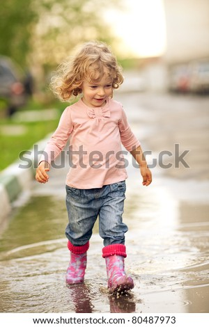 Cute child walking on puddle in autumn