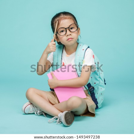 Cute child with book thinking and learning, studio shot isolated on colorful blue background, Creative of baby and genius concept