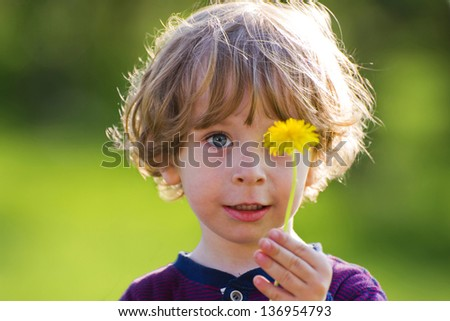 Cute child with dandelion on a green meadow