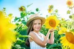 Cute child with sunflower in summer field. Enjoy nature girl bright photo, summer field sunflowers yellow flowers. Beautiful  child in light summer dress straw hat country life. Summer time concept.