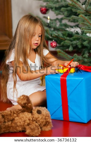 Cute Child with teddy bear toy finding her Christmas present in the morning still in her sleepwear and unwrapping it