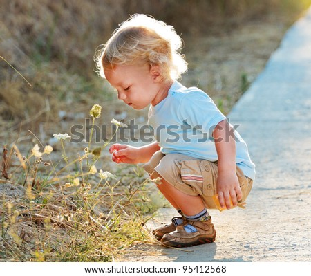 Cute child with wildflowers in sun back light