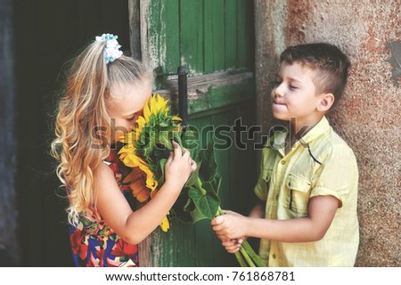 Free photos boy gives a girl flowersttle beautiful coupleds cute children a boy gives a girl flowers sunflower the concept of childhood thecheapjerseys Choice Image