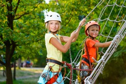 Cute children. Boy and girl climbing in a rope playground structure at adventure park