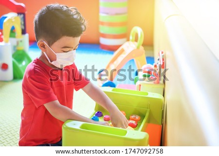 Cute children boy playing indoor  playground  with face mask protection. Children from kindergarten playing on playground. Self isolation. Stock photo ©