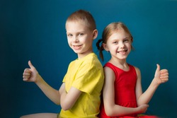 cute children brother and sister in bright clothes on a blue background