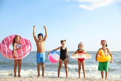Cute children enjoying sunny day at beach. Summer camp