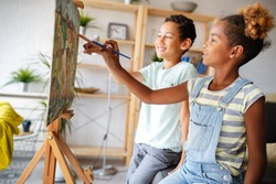 Cute children girl and boy painting together. Education, art, fun and creativity concept.