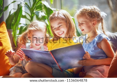 Cute children girls are reading a book sitting on sofa in room at home.