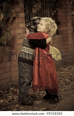 Cute children hugging each other at a park. Retro style. - stock photo