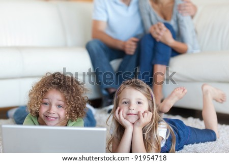 Cute children using a laptop while their parents are watching in their living room
