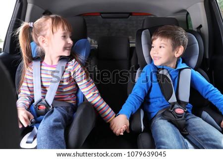 Cute children with fastened seatbelts in car