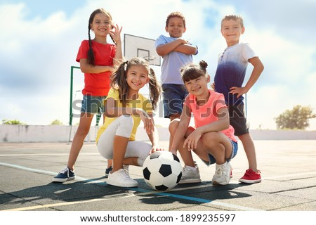 Cute children with soccer ball at sports court on sunny day. Summer camp