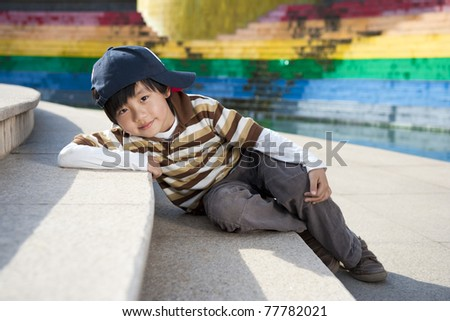 Cute Chinese boy model posing for camera on stairs
