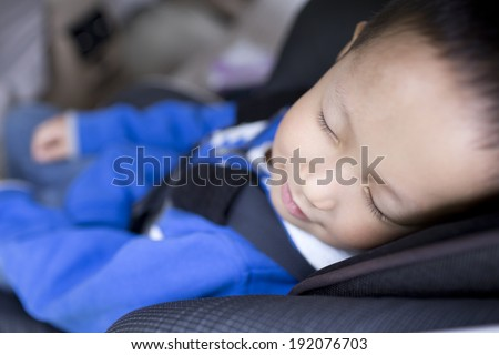 Cute Chinese boy sleeping in car within safety seat