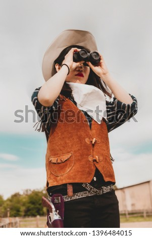 cute chinese cowgirl while looking at the horizon with binoculars on a wild west farm