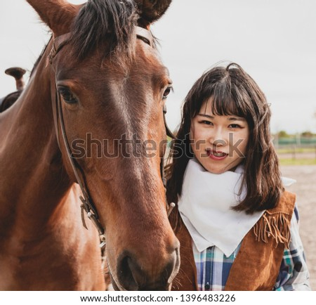 cute chinese cowgirl while taking care of her horse on a wild west farm