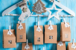 Cute Christmas Advent Calendar as small house with a number on blue wooden background