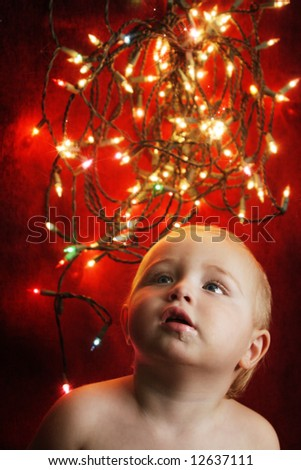 Cute Christmas Baby With Red Background And Lights Stock