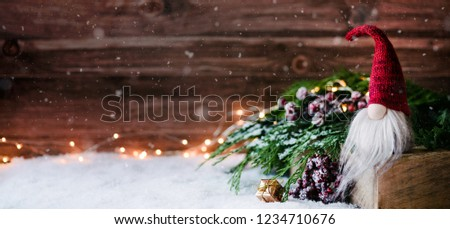 Cute christmas gnome is sitting and waiting for his presents for christmas - banner, header, headline format