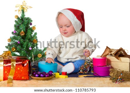 Cute chubby cherubic little baby in a Santa hat sitting surrounded by a Christmas tree and assorted shaped colorful gifts and decorations