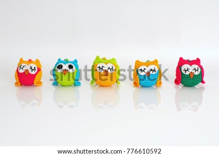Cute colorful handmade knitted owls placed on a white background
