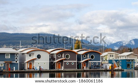 Cute, colourful floating houseboats line the docks in Mosquito Creek Marina, North Vancouver, British-Columbia. This alternative housing is growing in popularity with a challenging housing market.