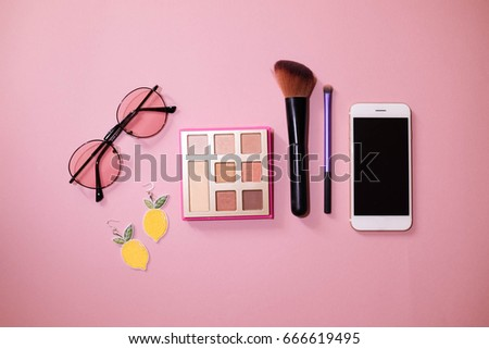 Cute concept : Flat lay with accessories  earring  pink sunglasses  eye shadow  make up brush and smartphone on pink pastel color