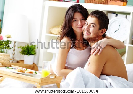 Cute couple enjoying a morning together having breakfast in bed