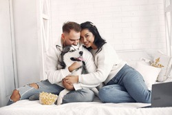 Cute couple in a bedroom. Lady in a white sweater. Pair watching a movie with a dog