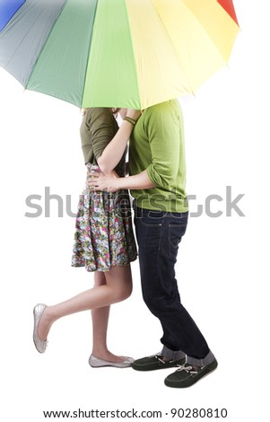Cute couple kissing under the umbrella isolated on white