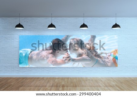 Cute couple kissing underwater in the swimming pool against room with poster display