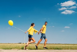 Cute couple running and holding hands. In background field. Girl holding yellow balloon. Dominating blue and yellow colors.