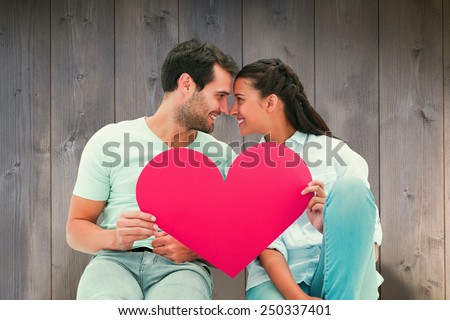 Shutterstock Cute couple sitting holding red heart against wooden planks