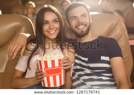 Cute couple sitting together in cinema, eating popcorn and watching comedy. Handsome bearded man hugging beautiful girlfriend sitting near while movie review. Concept of leisure and entertainment.