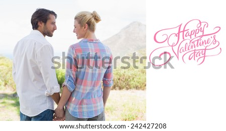 Cute couple standing hand in hand smiling at each other against happy valentines day