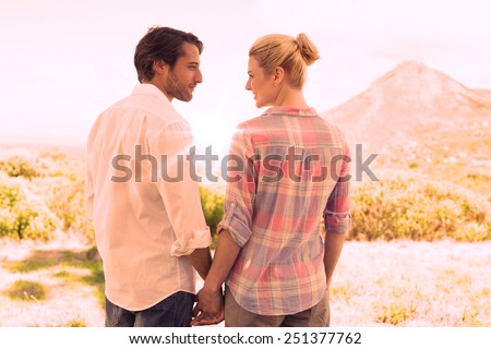 Cute couple standing hand in hand smiling at each other on a sunny day