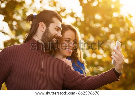 Cute couple using cellphone in the park with autumn / fall colors. #662596678