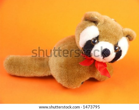 Cute cuddly brown raccoon toy. Brown raccoon - small toy animal on an orange background.