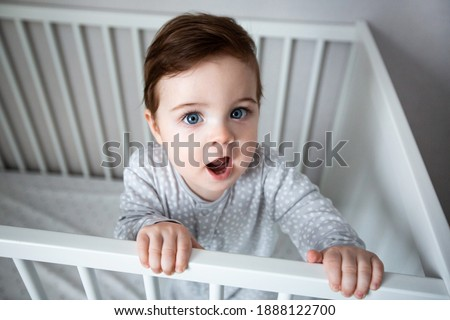 Cute curious baby standing in a white crib bed. White nursery for young children. Little boy learning to stand in his crib. Toys for infant cot. Smiling child playing in sunny bedroom top view Foto stock ©