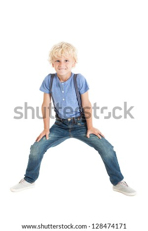 Cute curly blond boy wearing a blue shirt, suspenders, jeans and sneakers, jumping and waving his hands. Studio shot, isolated on white background.