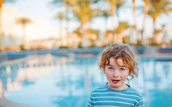 cute curly blond little boy on a background of a swimming pool in the vest. Summer vacation concept