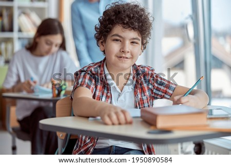 Cute curly boy writing test while sitting at desk in school classroom. Elementary school kids sitting on desks Stock photo ©