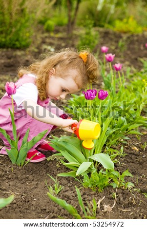 Cute curly girl watering flowers in the garden