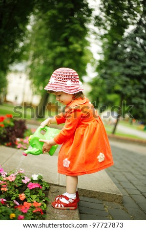 Cute curly girl watering flowers in the garden - stock photo