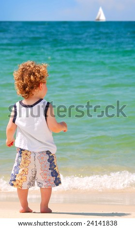 Cute curly haired toddler boy looking at sailboat on pretty ocean