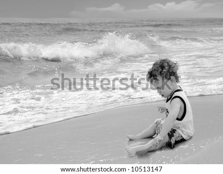 Cute curly headed boy playing with sand on pretty beach