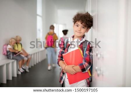 Cute curly schoolboy. Cute curly schoolboy with earphones on neck standing near lockers at school